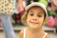 Little girl trying white cap in store Stock Images