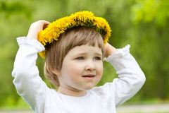 Little girl trying on yellow chaplet made of dandelions Royalty Free Stock Image
