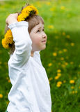 Little girl trying on yellow chaplet made of dandelions Stock Photos