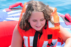 Little Girl Tubing. Young, happy girl getting ready to go tubing in the adriatic sea Royalty Free Stock Image