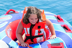 LITTLE GIRL TUBING. Young, happy girl getting ready to go tubing in the adriatic sea Royalty Free Stock Photography
