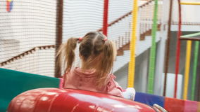 The little girl on the tubing rolls with slides in the play area stock video