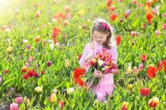 Little girl in tulip flower garden Royalty Free Stock Photo