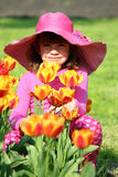 Little girl with tulip flowers Stock Image