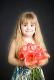 Little girl with tulips bouquet Stock Images
