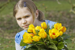 Little girl with tulips bouquet Stock Photo