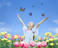 Little girl in tulips with hands up and butterfly
