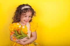 Little girl with tulips in hands on yellow background royalty free stock photography