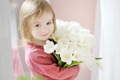 Little girl with tulips by the window Stock Photo