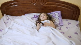 Little girl with a TV remote control. Little girl lying in bed with TV remote control stock video