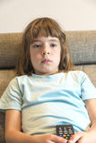 Little girl with TV remote control watching TV. Sitting on the couch Royalty Free Stock Photo