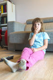Little girl with TV remote control watching TV Stock Photo