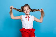 Little girl with two braids with colored pencils stock photography