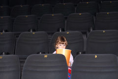 Little girl with two braids with popcorn sitting in cinema hall Stock Photos