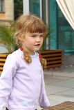 Little girl with two braids in summer cafe Royalty Free Stock Photo