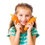 Little girl with two carrots Royalty Free Stock Photos