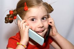 Little girl with two cellular phones. Little girl talking on two mobile phones and looks at camera Royalty Free Stock Image