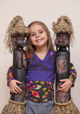 Little girl with two ethnic dolls. Four year old girl hugging doll-figurines from Africa Royalty Free Stock Image