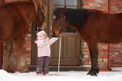 Little girl and two horses standing near the cottage door Royalty Free Stock Image