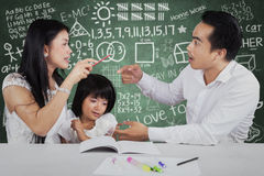 Little girl with two parents quarreling. Portrait of little girl crying while her parents quarreling when help their child to study Royalty Free Stock Images