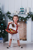 Little girl with two pigtails standing near a Christmas tree. She is holding a basket with toys Stock Photography