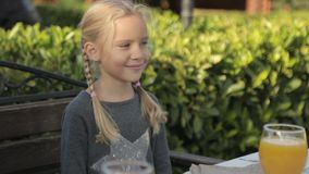Little girl with two plaits sitting at the table stock footage