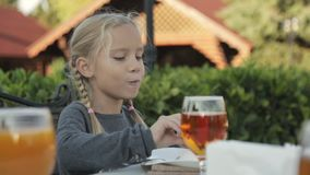 Little girl with two plaits sitting at the table in the outdoor cafe stock video footage