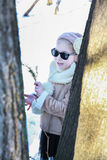 Little girl between two trees with a sprig of fir in hand Stock Image