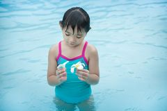 The little girl and two white flowers in the pool. The little girl and two white flowers. She`s in the pool and looking at the flowers in her hand Royalty Free Stock Photo