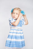 Little girl tying her hair in a tail. Little cute blond girl tying her hair in a tail on a white background Stock Image