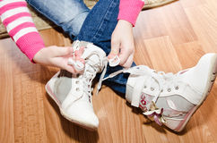 Little girl tying her white shoes at home Royalty Free Stock Images