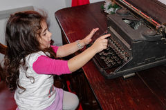 Little girl with a typewriter Stock Photos