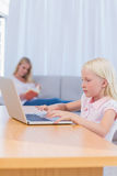 Little girl typing on laptop in the living room Royalty Free Stock Photography