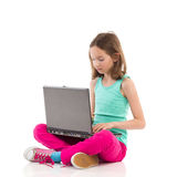 Little girl typing something on a laptop Stock Image