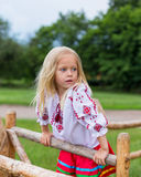 Little girl in ukrainian clothes on the hedge. Little girl in ukrainian traditional clothes on the hedge in village Royalty Free Stock Image