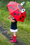 The little girl with an umbrella. And in rubber boots Stock Image