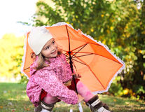Little girl with umbrella in autumn park Royalty Free Stock Image