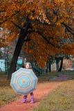 Little girl with umbrella autumn season Stock Photo
