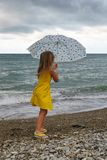 Little girl with umbrella on beach in bad weather. Little girl with umbrella on beach. She looks at surf during storm. Man is unrecognizable stock image