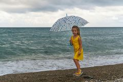 Little girl with umbrella on beach in bad weather. Little girl with an umbrella walks along beach. Curtains on sea waves and clouds royalty free stock photo