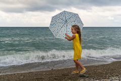 Little girl with umbrella on beach in bad weather. Little girl with an umbrella walks along beach. Curtains on sea, waves and clouds. Strong wind pulls umbrella stock photo