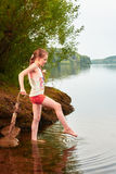 Little girl with an umbrella in cloudy day near the lake Stock Photos