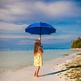Little girl with umbrella on exotic beach Royalty Free Stock Image