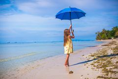 Little girl with umbrella on exotic beach Royalty Free Stock Photography