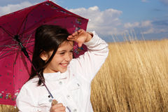 Little girl with umbrella in the field stock photos