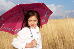 Little girl with umbrella in the field. Autumn time stock photography
