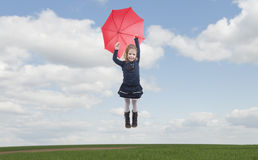 Little girl with umbrella flying in the air Royalty Free Stock Photos