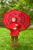 Little girl with umbrella in park Stock Photos