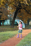 Little girl with umbrella in park Stock Image