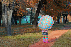 Little girl with umbrella in park Royalty Free Stock Photos